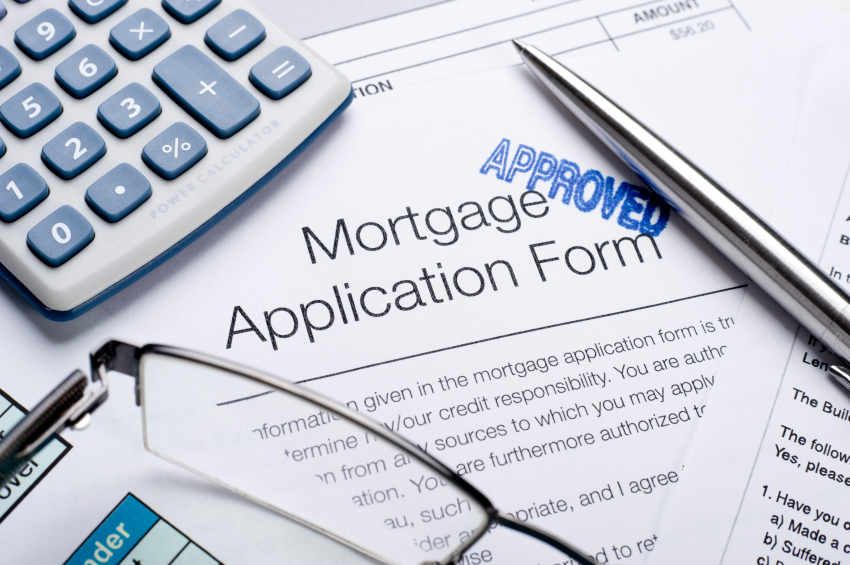 Approved Mortgage application form with a calculator, pen and glasses