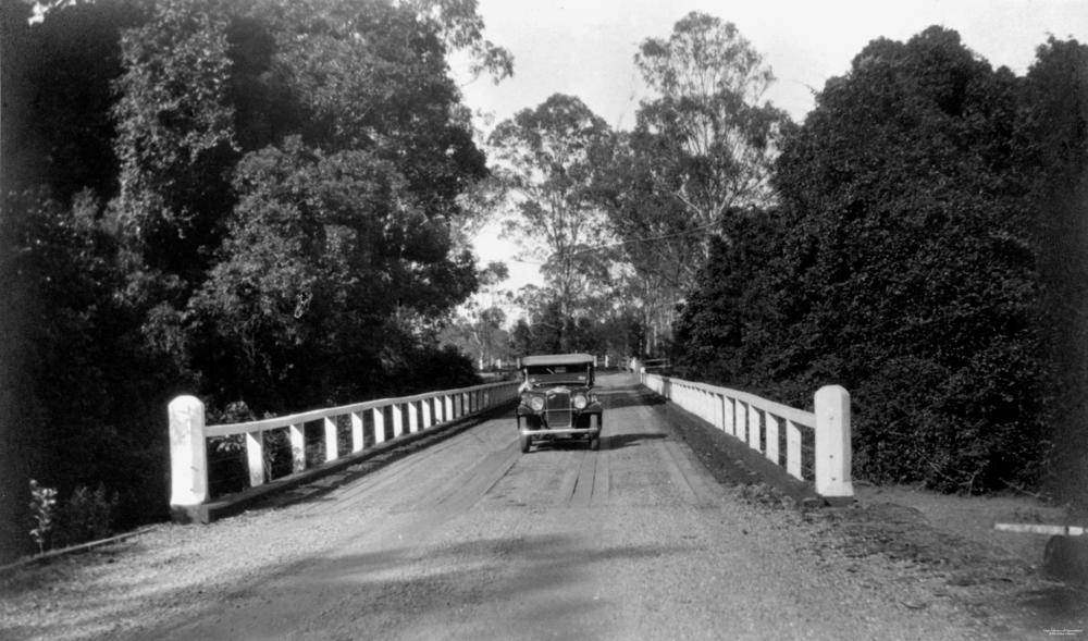 Austin motor vehicle crossing a bridge on the North Coast Road at Burpengary, 1934